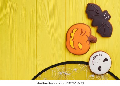 Assorted Hallowen cookies on yellow background. Halloween holiday sugar biscuits including pumpkin, bat and Jack Skellington with copy space.
