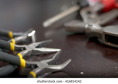 Assorted Hand Tools On Dark Wood Surface