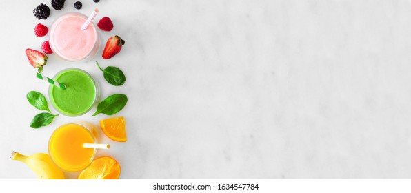 Assorted healthy smoothies. Top view side border banner against a marble background. Strawberry, green and orange. Copy space.