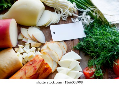 Assorted homemade cheesy Pasta filata, Provolone, in various shapes and sizes on the wooden background, suluguni, pigtail, Caciocavallo with tomatoes and empty blank for logo of a home cheese factory