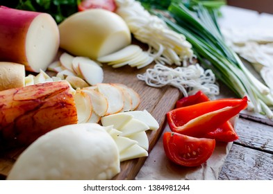 Assorted homemade cheesy Pasta filata, Provolone in various shapes and sizes on the wooden background, suluguni, pigtail, Caciocavallo with tomatoes and herb
