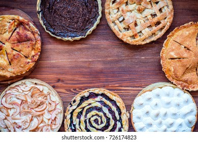 Assorted homemade rustic american style apple, berry, chocolate and lemon meringue pies, top view, copy space