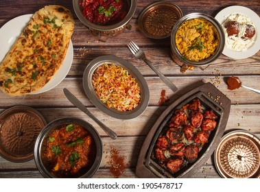 Assorted Indian dishes of rice and curry on wooden background. Top view