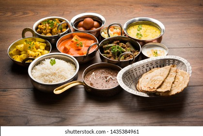 Assorted Indian food like paneer butter masala, dal, roti, rice, sabji, gulab jamun and bound raita served in bowls over moody background, selective focus