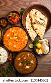 Assorted indian food for lunch or dinner, rice, lentils, paneer, dal makhani, naan, green salad, spices over moody background. selective focus