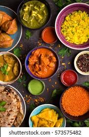 Nourriture indienne assistée sur fond bois foncé. Plats et entrées de la cuisine indienne. Curry, poulet au beurre, riz, lentilles, paneer, samosa, naan, chutney, épices. Boules et assiettes de cuisine indienne