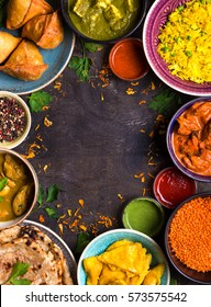 Assorted indian food on dark wooden background. Dishes of indian cuisine. Curry, butter chicken, rice, lentils, paneer, samosa, naan, chutney, spices. Space for text. Bowls and plates with indian food