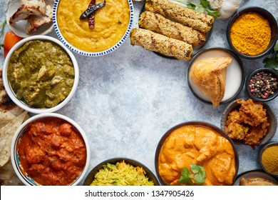 Assorted indian food on stone background. Dishes of indian cuisine. Tikka masala, butter chicken, Nilgiri, seekh kebab, rice, Onion Bhajia, paneer, samosa, naan, Daal Tarka, spices With copy space