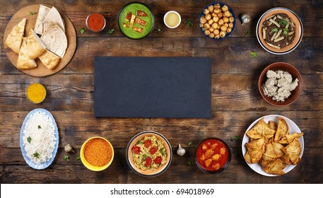 Assorted indian food on a wooden background. Dishes and appetizers of indian cuisine. Curry, butter chicken, rice, lentils, palak paneer, samosa, naan, chutney, spices. Bowls plates with indian food