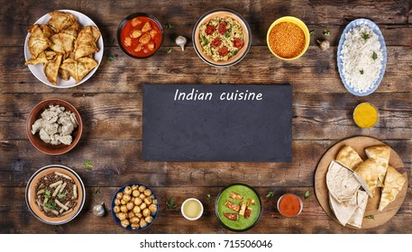 Assorted indian food on a wooden background. Dishes and appetizers of indian cuisine. Curry, butter chicken, rice, lentils, palak paneer, samosa, naan, chutney, spices. Bowls and plates