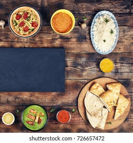Assorted indian food on wooden background. Dishes and appetizers of indian cuisine. Curry, butter chicken, rice, lentils, palak paneer, samosa, naan, chutney, spices. Bowls and plates with indian food
