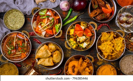 Assorted indian food set on wooden background. Dishes and appetisers of indeed cuisine, rice, lentils, paneer, samosa, spices, masala. Bowls and plates with indian food top view