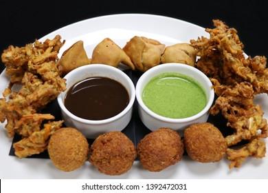 assorted indian snack pakora plater with paneer balls, onion crisps and panjabi samosa
