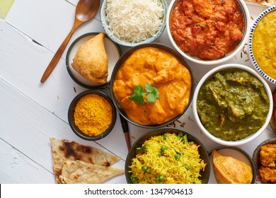 Assorted Indian various food with spices, rice and fresh vegetables on white wooden table. Flat lay. Top view.