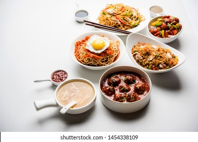 Assorted Indo chinese food in group includes non vegetarian or chicken Schezwan/Szechuan hakka noodles, fried rice, manchurian, egg american chop suey, soup with spoon and chop sticks, selective focus