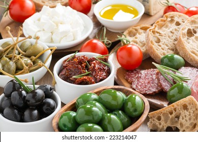 assorted Italian antipasti - olives, salami, pickles and bread, close-up