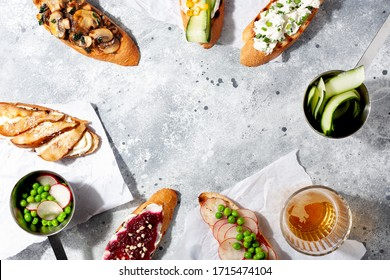 Assorted italian appetizer bruschetta or tapas set with different savory and sweet topping on gray concrete background.Top view,copy space