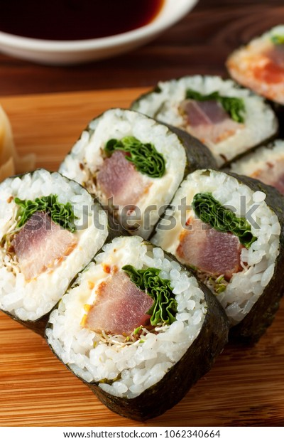 Assorted japanese sushi on wooden rustic background. Sushi rolls, pickled ginger, soy sauce. Asian or Japanese food