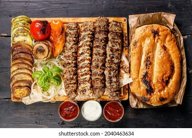 Assorted kebabs from different types of meat. Veal, chicken, lamb kebabs with vegetables and sauces on a wooden board. Traditional Turkish street food. Food delivery service concept. Top view