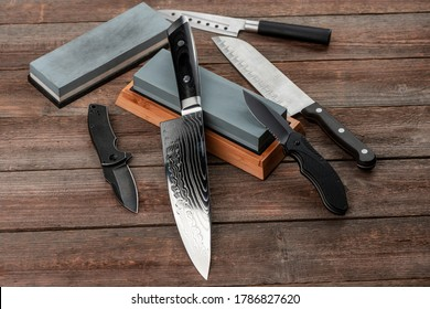 Assorted knives and sharpening stones on a rustic wooden table, top view. Jackknife, cheese knife, Santoku and chef's knife.