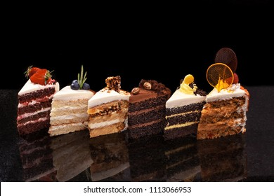 Assorted large pieces of different cakes: chocolate, raspberries, strawberries, nuts, blueberries. Pieces of cakes on a black table.