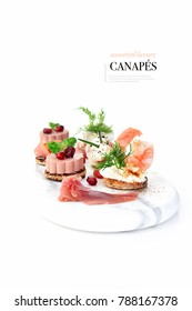 Assorted luxury styled canapes with pate, prawns, parma ham and jamon iberico de bellota with dill, chives and pomegranate. Shot against white with accommodation for copy space.
