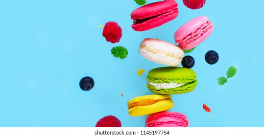 Assorted macaroons falling cookies with berries close up on blue background