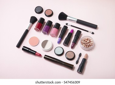 Assorted make up and beauty products arranged on a baby pink background