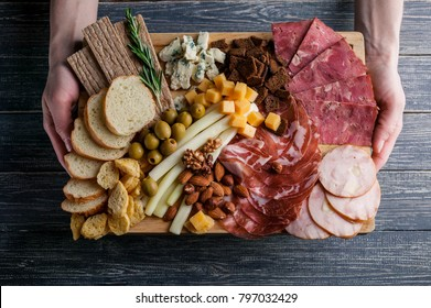 Assorted from meat and cheese on a chopping board. Smoked sausage, meat roll from a turkey with cheese, jamon, olives, nuts and various grades of cheese. Soft focus. Low key.