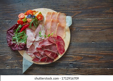Assorted meat delicacies, cut into thin slices on a round wooden Board. Decorated with bruschetta with vegetables and fresh herbs