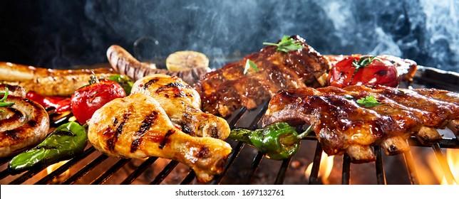 Sorgfältiges Grillen auf einem Grillplatz im Freien in einem flachen Blickwinkel auf Hühnerbeine, Schweinegrippen, Würste und Gemüse mit steigendem Rauch und Kopienraum auf einem Panoramabanner