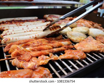 Assorted meat on grill. Various sausages, meat rolls, fresh raw meat steaks and grilled tofu. Grilling on the open air. Summer food concept. Barbecue, side view.