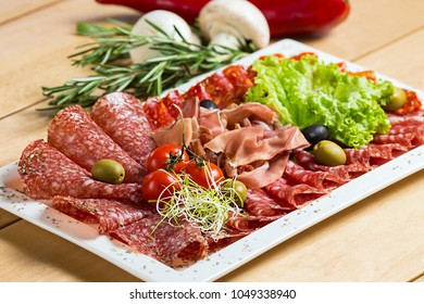 Assorted meat and sausages on a white plate with cherry tomatoes and olives