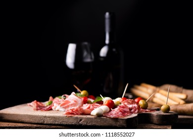 Assorted meats and  cherry mozzarella cheese, on a wooden cutting board with bottle of wine and glass on background. Italian antipasti