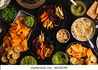 Assorted mexican style buffet Snacks baked carrots chips corn chips nachos Guacamole Salsa Quinoa bowl