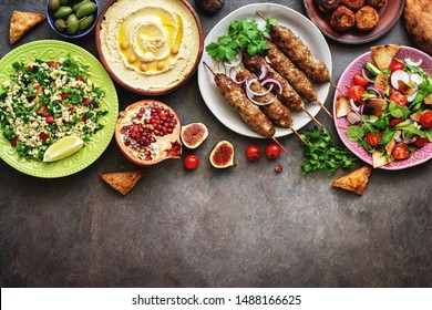 Assorted Middle Eastern and arabic dishes on a dark rustic background. Hummus,tabbouleh, salad Fattoush,pita,meat kebab,falafel,baklava,pomegranate. Halal food.Top view, flat lay, copy space.