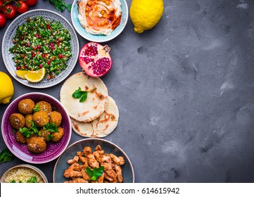 Assorted middle eastern dishes and meze background. Tabbouleh, meat shawarma, hummus bowl, falafel, pita, bulgur, lemons. Arab cuisine. Party food. Middle eastern dinner. Space for text. Top view