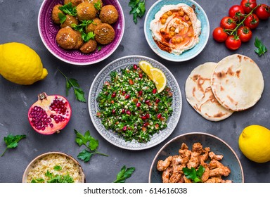 Assorted middle eastern dishes and meze. Tabbouleh salad, meat shawarma, hummus bowl, falafel, pita, bulgur, pomegranate, lemons. Arab cuisine. Party food. Middle eastern dinner. Ethnic food. Top view