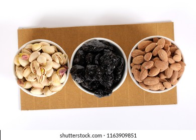 Assorted nuts on white, dry fruits, mix nuts, roasted almond, prunes, pistachio