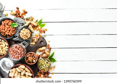 Assorted nuts on a white wooden background. Top view. Free space for your text.