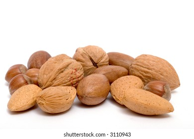 assorted nuts with realistic drop shadows for depth on white background. Contains hazel, almond, walnut and pecan