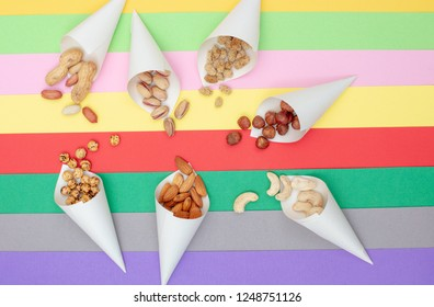 Assorted nuts served in paper cones scattered on a colorful paper background top view
