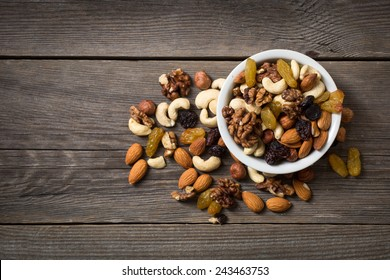 Assorted nuts in white bowl on wooden surface.