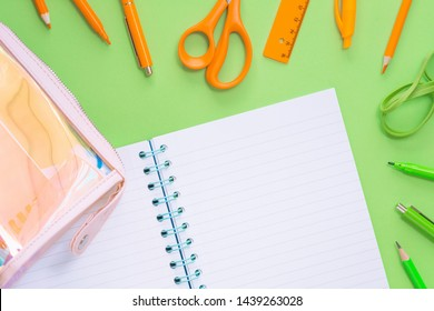 Assorted office and school orange and green stationery as border with notebook and iridescent pencil case. Flat lay with copy space for back to school or education and craft concept