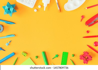 Assorted office and school red green blue and white stationery and brain teasers on yellow background. Flat lay with copy space for back to school or education and craft concept. Border or frame