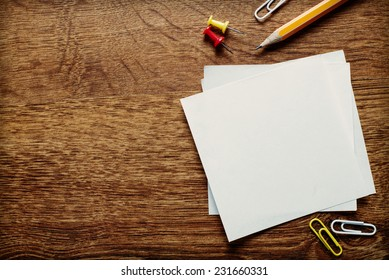 Assorted Office Supplies such as Clean Papers, Pencil, Thumbtacks and Clips on the Wooden Table, Resting at the Bottom Edge with Copy Space Above for Texts.