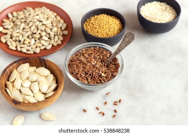 Assorted oil seeds (flax, sesame, pumpkin, sunflower, mustard) in small bowls on stone background - organic ingredients for healthy vegetarian vegan nutrition