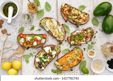 Assorted  open faced sandwiches, Open avocado sandwiches made of  slices of sourdough bread with  various toppings on a white wooden table, top view