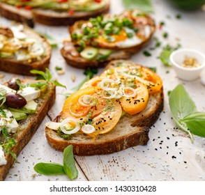 Assorted open faced sandwiches, in the middle of board an open avocado sandwich made of slice of sourdough bread with the addition of yellow tomato, green pesto, slice onion, close-up