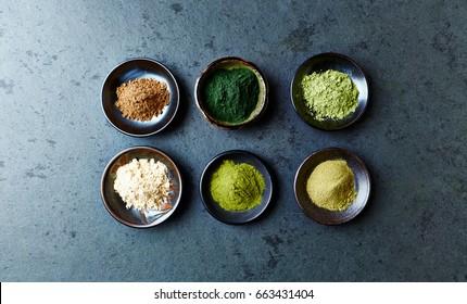 Assorted organic Super Foods. Siberian ginseng, chlorella, green barley, maca, green oat, kale powder. Flatlay